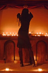 Koffin Kitty stands facing two rows of lit candles with her hands raised over her head.