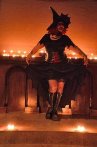 Bat Wing lifts the hem of her skirt playfully in both hands as she stands in front of a candle-lit altar.