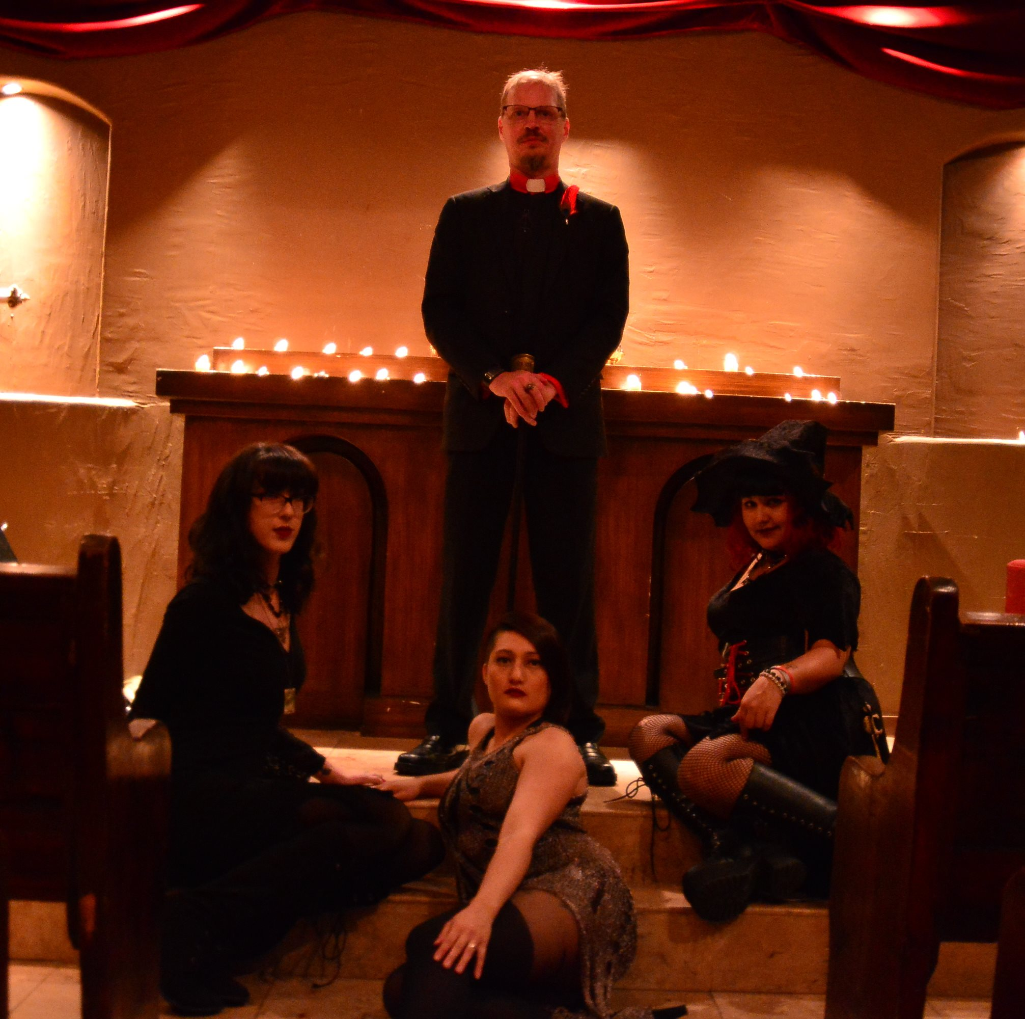 Brother Slim stands in front of a candle lit altar, with Koffin Kitty, Snake Oil, and Bat Wing sitting on the steps at his feet.