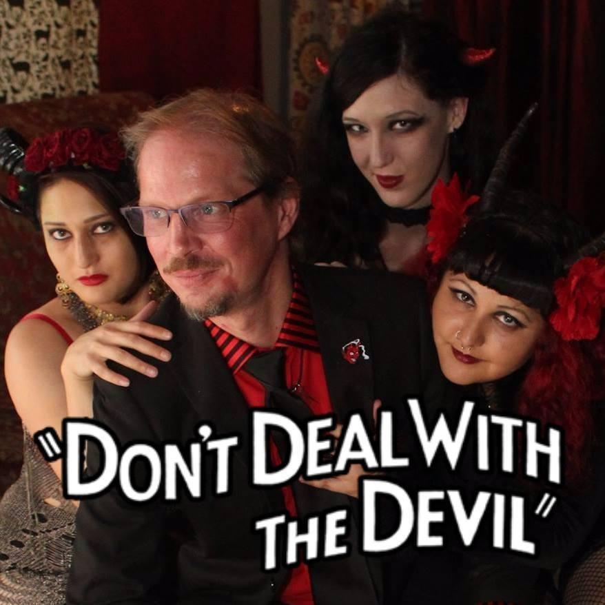"Brother Slim poses surrounded by Bat Wing, Snake Oil, and Koffin Kitty with the words ""Don't Deal With the Devil"" superimposed over the lower third of the image."
