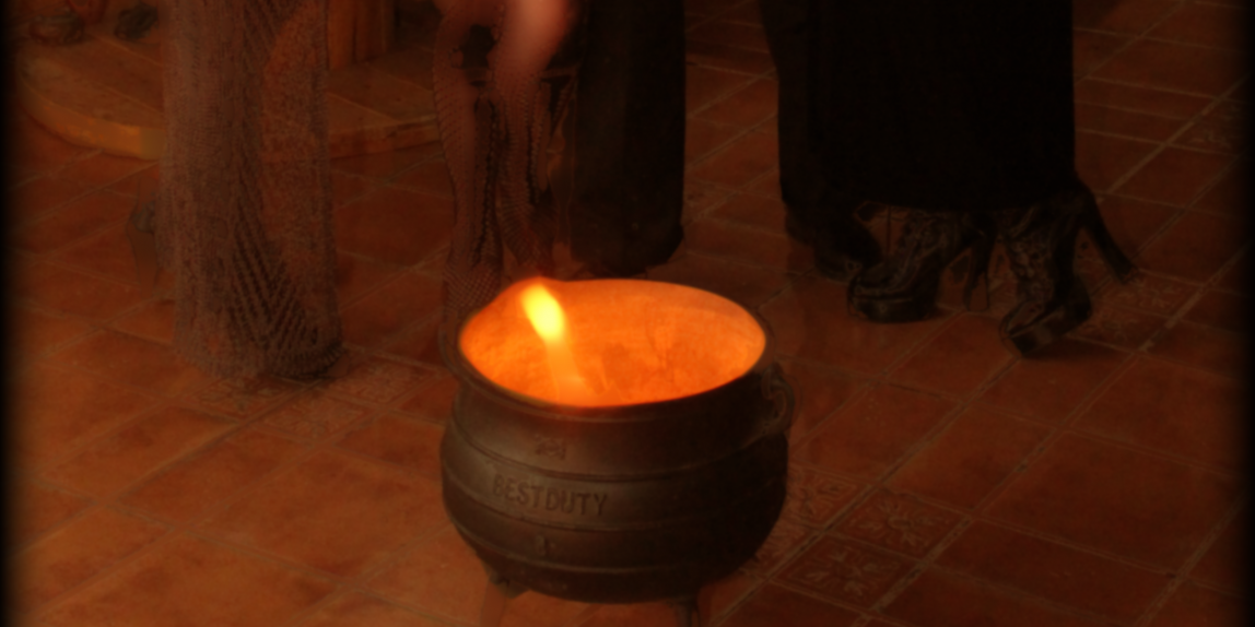 An iron cauldron containing a small flame stands in front of the legs of three women in long dresses.