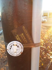 A business card for the Sin City Satanic Revival tucked into a metal band around a sign post.
