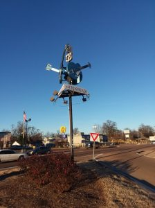 "An intersection with a sign post that reads ""The Crossroads."" The post is toped by two blue guitars."