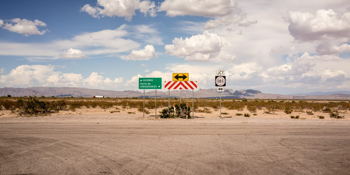 "A desert road ending in a T-intersection, with directional signs to ""Truth and Consequences"" and ""Socorro."""